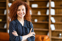 Ambitious Smiling Young Curly Woman Standing In The Office Space With Her Arms Crossed And Looking At Camera, Charming Red-haired Female Student In The Library, Succesful Female Entrepreneur Indoors