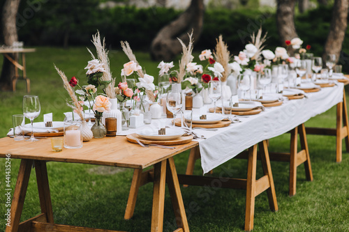 Fotografie, Obraz A large wooden, long, decorated with flowers, reeds, empty dishes, plates, forks, knives, glasses with a white tablecloth stands on the green grass in the forest