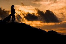 Unrecognizable Pregnant Woman Standing On Hill At Sunset