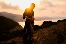Pregnant Woman Standing On Hill At Sunset
