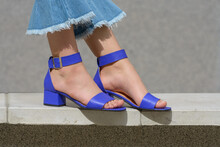 Women's Legs In Blue Denim Jeans And Sandals In The City Street. Trendy Elegant Casual Outfit. Details Of Everyday Summer Look.
