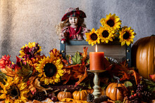Fall Scene With Orange Pumpkins Yellow Sunflowers Burning Candle And Young Girl Doll