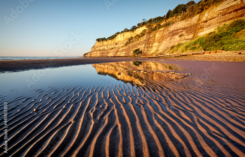 Fotografia Shanklin beach on the isle of wight, with ripples in the sand and reflection of cliffs in the pool of water