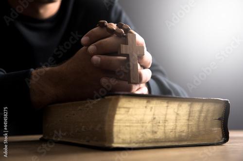 Fototapeta prayer man holding Bilbe with cross