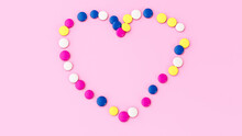 3D Rendering Of Colorful Chocolate Button Candy In A Heart Shape On A Pink Background
