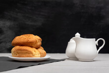 Homemade Eclairs And Creamer. Traditional French Eclairs. Gray Background