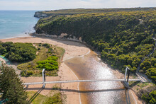 Aerial View Of A Footbridge Over A Murky River Running Out To Sea