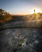 Hiker On A Rocky Peak At Sunrise