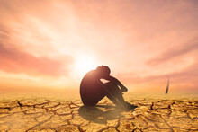 People Sit With Their Heads Down And Hopeful In A Dry Land Because Of The Drought There Is No Rain For A Long Time. Global Warming And Drought Concept