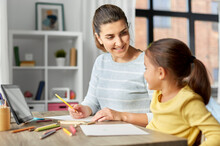 Family, Motherhood And Leisure Concept - Mother Spending Time With Her Little Daughter Drawing With Color Pencils At Home
