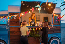 Young Women Ordering At Food Truck Bar