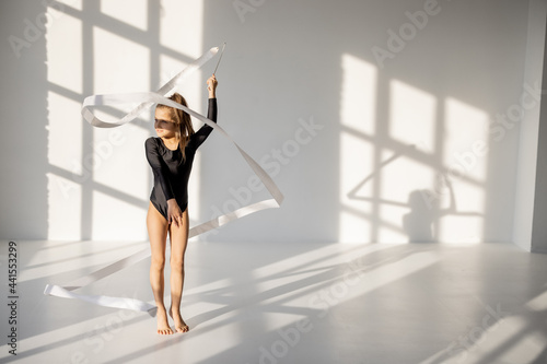 Fotografiet Little girl practising rhythmic gymnastics with a gymnastic tape at white sunny dance room