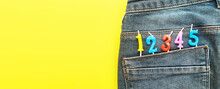 Birthday Candles Sticking Out Of The Back Pocket Of Blue Jeans On Yellow Background