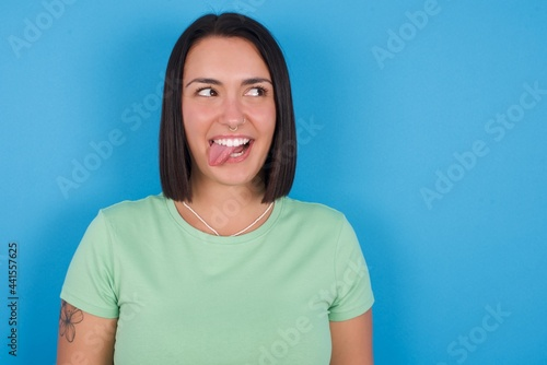 Fotografie, Obraz young beautiful brunette girl with short hair standing against blue background showing grimace face crossing eyes and showing tongue