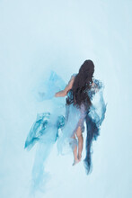 Abstract Portrait Of A Girl Swimming In Blue Dress In Pool Like An Angel