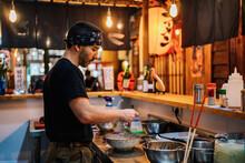 Man Serving Dish In Asian Restaurant