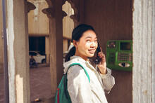 Asian Woman Using A Phone Booth On The Street