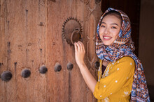 Asian Woman Next To An Old Wooden Door