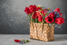 Summer Or Spring Bouquet Of Daffodils And Red Tulips  In A Wicker Basket Located On A White Background. Blossom Of Spring Flowers.