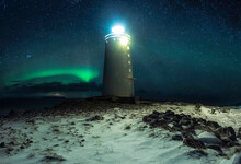 Lighthouse Against Starry Sky In Winter Countryside