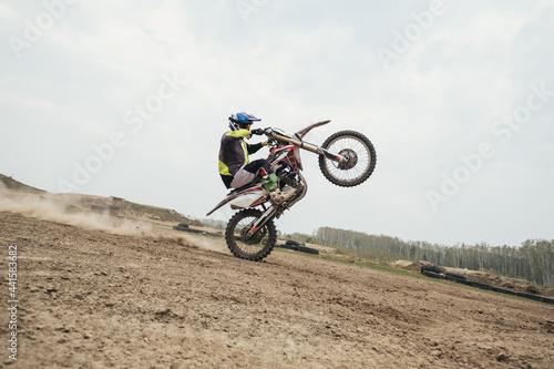 Fotografia Motorcyclist jumping and riding on rear wheel at enduro motocross training groun