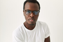 Close Up Image Of Handsome Young Dark Skinned Man With Trimmed Stubble Posing Isolated Wearing Stylish Glasses And White Tee Looking At Camera With Confident Facial Expression. Eyewear And Vision