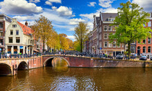 Netherlands Amsterdam. View At River Amstel With Traditional Houses At Bank And Boats At Water Canal. Scenic Cityscape. Spring Day With Blue Sky And White Clouds.