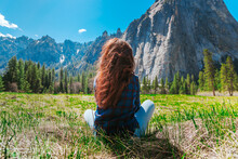 A Young Woman In Jeans Sits On The Grass With An Amazing View Of The Mountains In Yosemite National Park