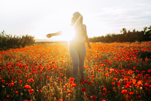 Woman Standing On Field With Red Flowers In Sunny Day
