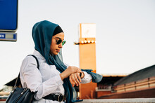 Ethnic Woman Checking Time On Wristwatch And Waiting For Train