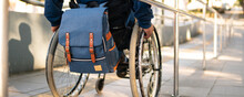 Detail Of Black Man In Wheelchair Going Down The Ramp.