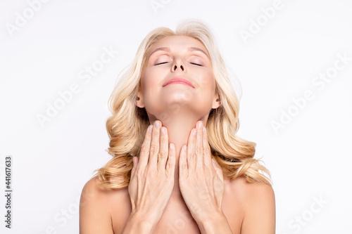 Fotografie, Obraz Portrait of attractive dreamy woman touching neck applying cream moisturizing we