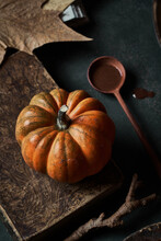Small Pumpkin On Wooden Table Decorated With Spoon And Leaves