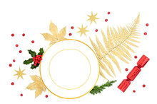 Christmas Place Setting Abstract Layout With Porcelain Plate, Gold Leaves, Holly With Loose Berries, Fir, Stars And Xmas Cracker On White Background. Festive Design For  Xmas And New Year. Top View.