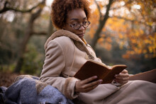 Serene Young Woman Reading In Autumn Park