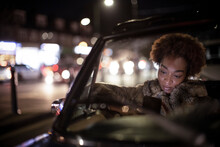 Young Woman Using Smart Phone In Convertible At Night