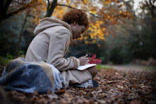 Young Woman Journaling In Tranquil Autumn Park