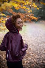Portrait Happy Young Woman Jogging In Autumn Park
