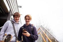Happy Teenage Boys Using Smart Phone On Steps