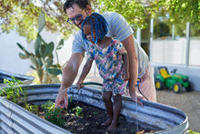 Father And Cute Daughter Watering Plants In Backyard