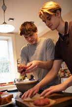 Teenage Boys Making Hamburger Patties In Kitchen