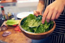 Close Up Teenage Boy Making Spinach Salad At Home
