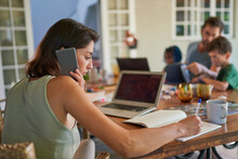 Woman Working From Home At Dining Table With Family