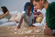 Brother And Sister Playing With Scrabble Tiles At Home