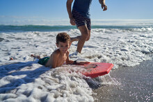 Happy Boy Body Boarding In Sunny Summer Ocean Surf