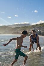 Happy Playful Father Splashing Son In Sunny Summer Ocean
