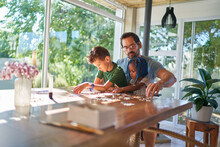 Father And Kids Assembling Jigsaw Puzzle At Dining Table