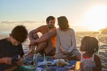 Happy Couple Enjoying Picnic With Kids On Sunny Summer Beach