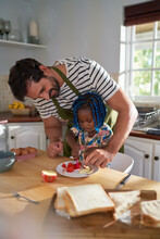 Father Helping Daughter Cut Fruit In Kitchen