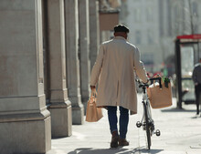 Man With Bicycle And Grocery Bags Walking On Sunny Sidewalk